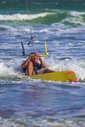 Athletic man riding on kite surf board sea waves Kuvituskuvat