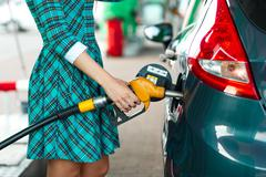 Woman fills petrol into her car at a gas station Kuvituskuvat