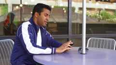 Young male sitting out outdoor table waits for someone to arrive 4k - stock footage