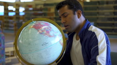 Young college student exploring world globe in library 4k Stock Footage
