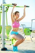 Woman exercising with exercise equipment in the public park by the sea Stock Photos