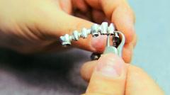 Dental technician measures the metal false teeth for dental prosthesis close up Stock Footage
