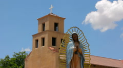 Statue of the Our Lady of Guadalupe in front of an Adobe Church Stock Footage