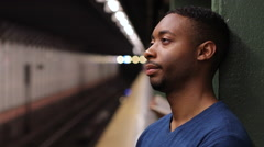 Young African American black man in city tired at subway platform Stock Footage