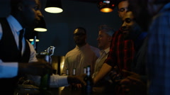 4K Happy mixed ethnicity male friends drinking beers at the bar in nightclub Stock Footage