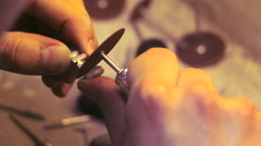 Dental technician grinds metal teeth for false dental prosthesis close up - stock footage