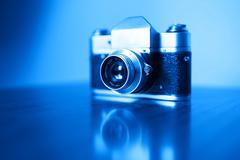 Horizontal vintage blue rangefinder camera background - stock photo