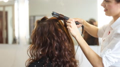 young woman and hairdresser with hair iron making hairdo at hair salon - stock footage