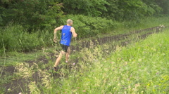 Slow motion. Male runner exercising and training outdoors in nature. traill-r Stock Footage