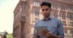 Young southeast Asian Indian man in City using tablet computer Stock Footage