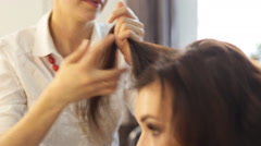Young woman and hairdresser with hair iron making hairdo at hair salon Stock Footage