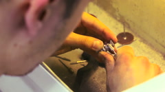 Dental technician grinds metal teeth for false dental prosthesis close up - stock footage