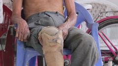 Close-up disable old man with prosthesis sitting on the chair Stock Footage
