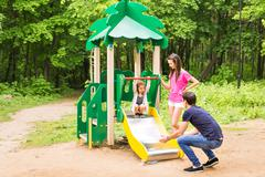child with parents at the playground. Mom, dad and daughter. playing family - stock photo