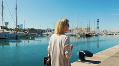 Woman in sunglasses walking along the waterfront with yachts. Rear view, the bay Stock Footage