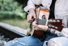 Teenager hands on the guitar strings close up image Stock Photos