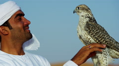 Arabic man with trained bird of prey standing on desert sands Stock Footage