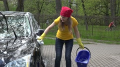 Pretty woman washes her car with sponge in open air Stock Footage