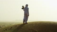 Sunset silhouette Arabic man with bird of prey on desert sands Stock Footage