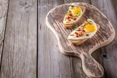 scrambled eggs with bread on cutting board - stock photo