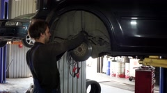 Male worker repairing automobile brake system at work Stock Footage