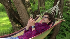 The resort in the hammock man using phone Stock Footage