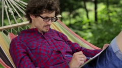 A man in a hammock drawing on paper Stock Footage