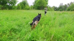 Happy young woman running with her German Shepherd dog. Slow motion. Stock Footage