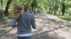 Girl runs through the park in the morning.Sport and music, young woman Stock Footage