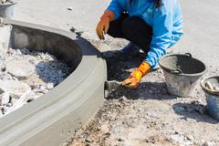 The worker apply cement over the surface of footpath edge - stock photo