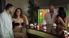 Girls and boys drinking tea and relaxing in sauna at aquarium background Stock Footage