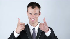 Young business man shows thumbs up with both hands while smiling. Stock Footage