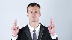 Young man making a wish with cross fingers Stock Footage