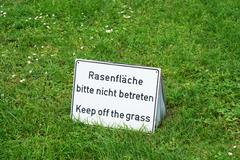 Bilingual keep of the grass sign in Germany Stock Photos
