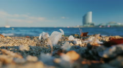 Debris and dirt on the beach the background sea and the promenade of Barcelona Stock Footage