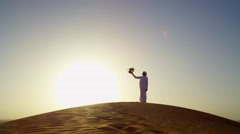Falcon tethered to male owner in traditional Arabic dress sunset silhouette Stock Footage