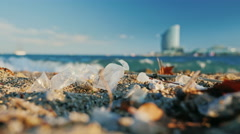 Garbage on the beach, tourists feet are in the sand. Barcelona, Spain Stock Footage