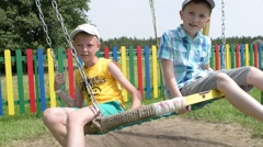 Two boys ride on a swing in the park playground Stock Footage