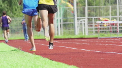 Two runners on a stadium track - slow motion, back view Stock Footage