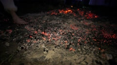 Man with bare heels stepping on hot coals Stock Footage