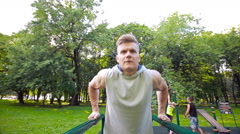 Young man in good physical shape, is engaged on the bars Stock Footage