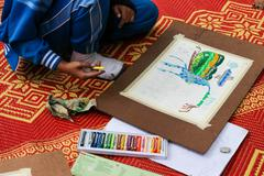The asian boy is painting crayon color on her drawing for drawing contest. Stock Photos