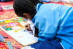 The asian girl is painting crayon color on her drawing for drawing contest. - stock photo