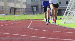 Two runners on a stadium track - slow motion, feet level Stock Footage