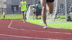 An athletes run on a stadium track - slow motion Stock Footage