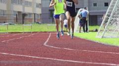 Two athlete run on a stadium track - slow motion, feet level Stock Footage