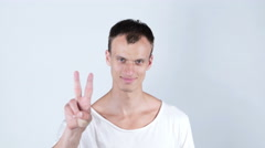 Portrait of young man smiling and showing you victory sign on white background Stock Footage