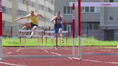 Two young athletes run and jump over a hurdles on a stadium track - slow motion Stock Footage