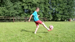 Boy soccer player fills the ball down on the green field Stock Footage