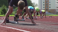 A start of young runners on a start line on a stadium - slow motion, feet level Stock Footage